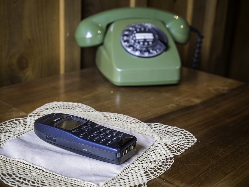 green rotary phone beside black and gray cordless home phone