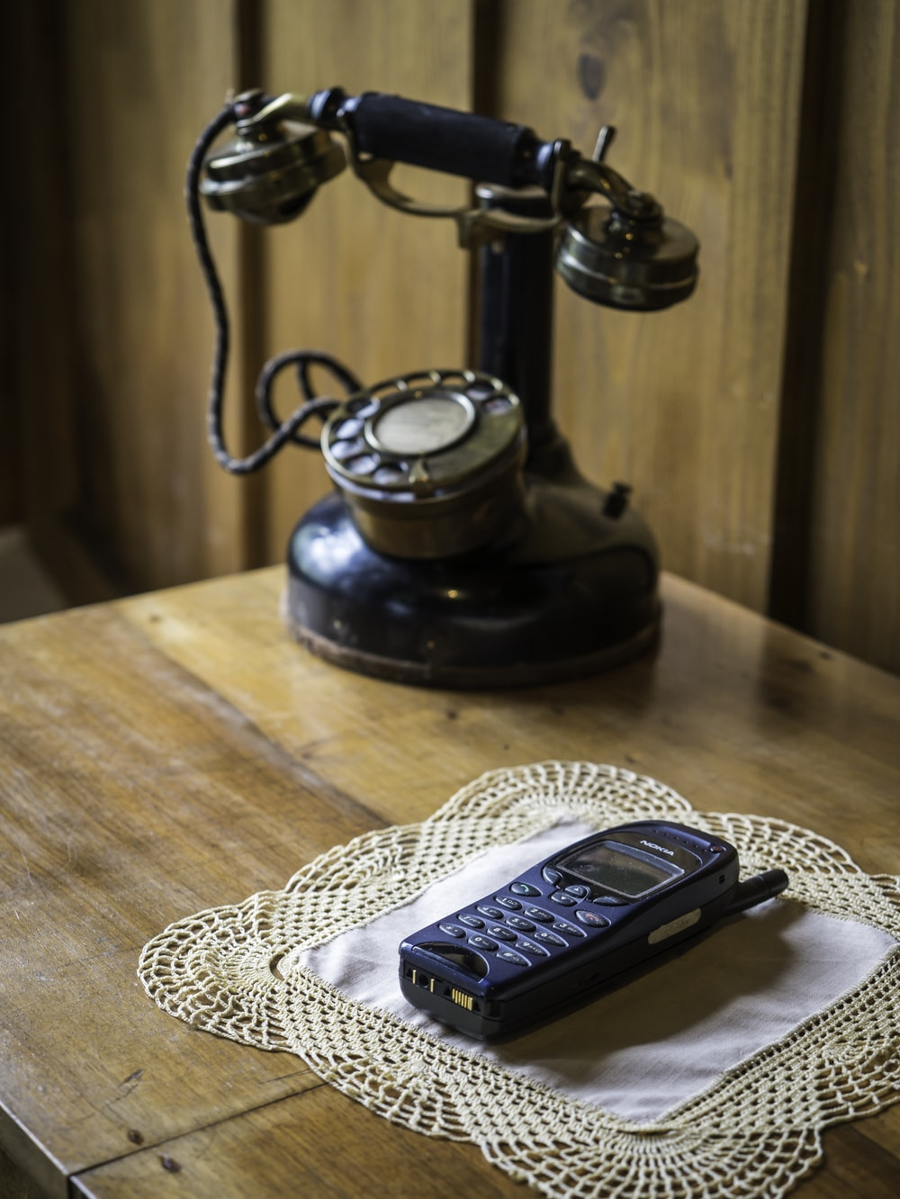 black and silver desk phone on white knit table mat