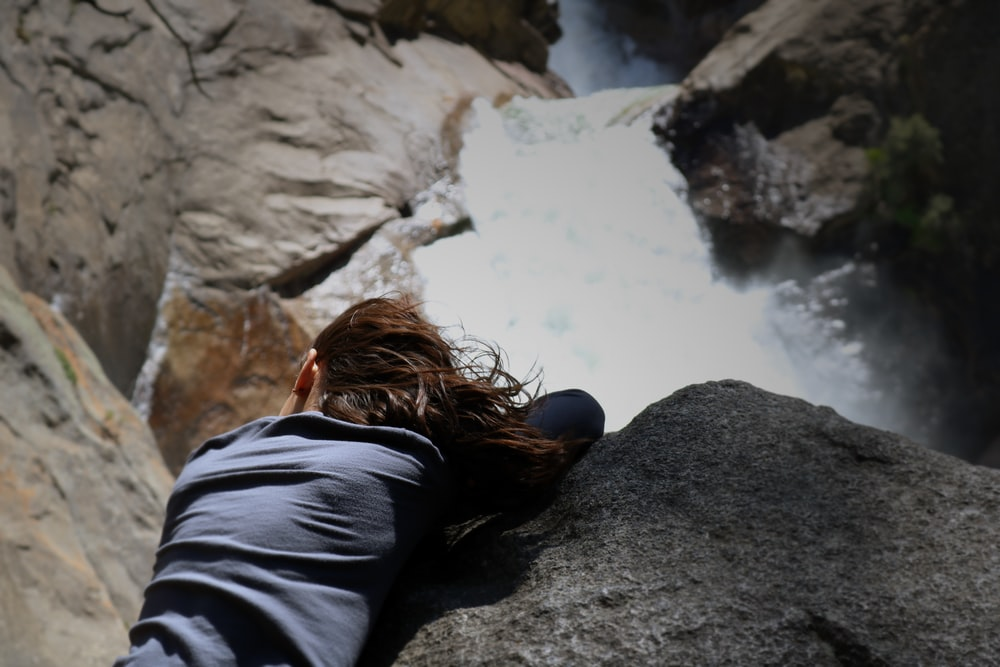 woman in black jacket sitting on rock near river during daytime