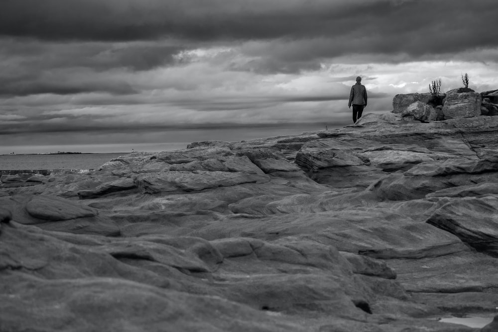 grayscale photo of man standing on rock formation near sea