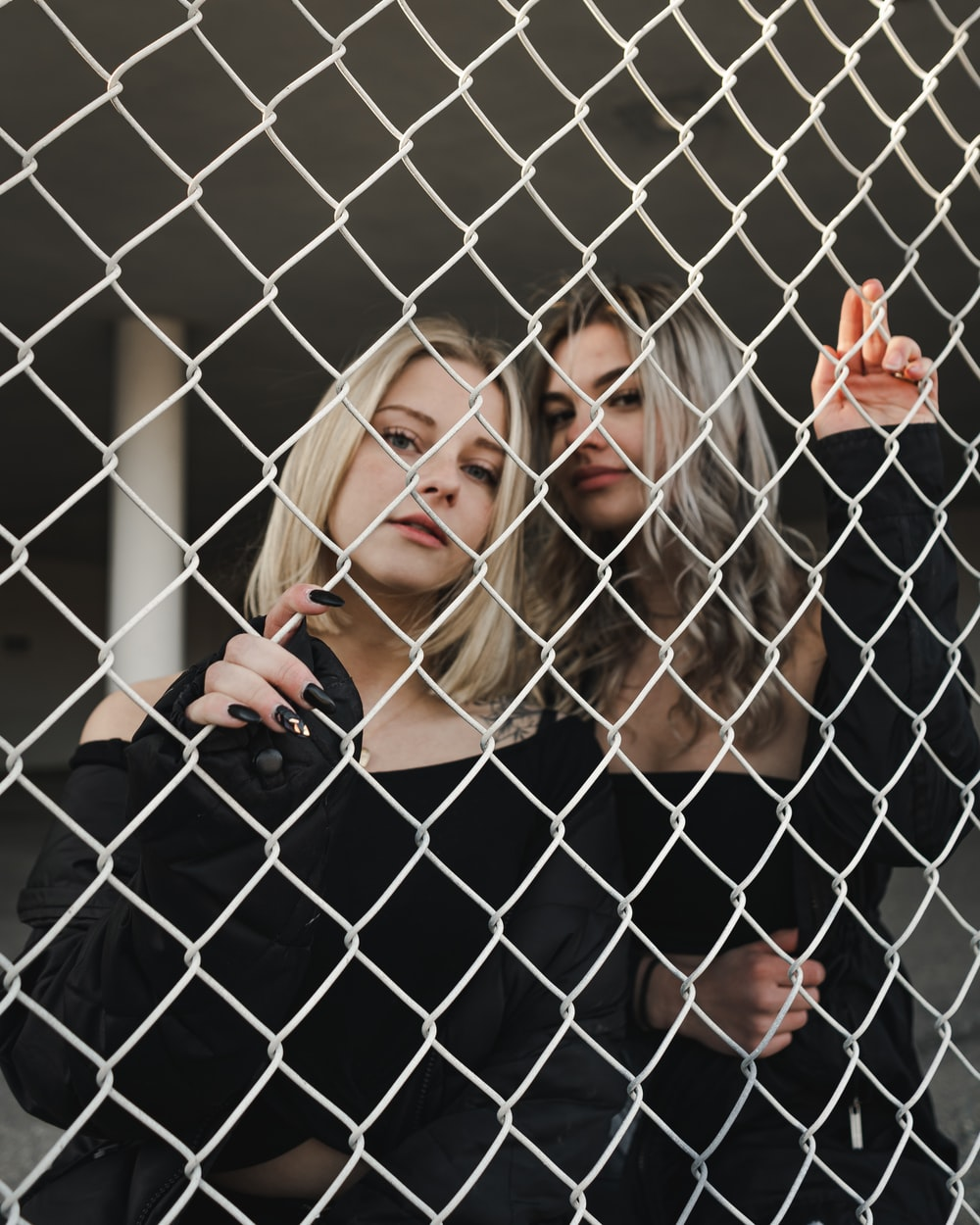 woman in black long sleeve shirt leaning on chain link fence