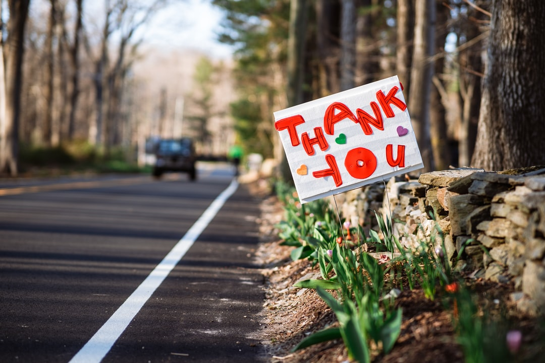 A sign o the side of a road marked with bold red letters exclaiming Thank you.
