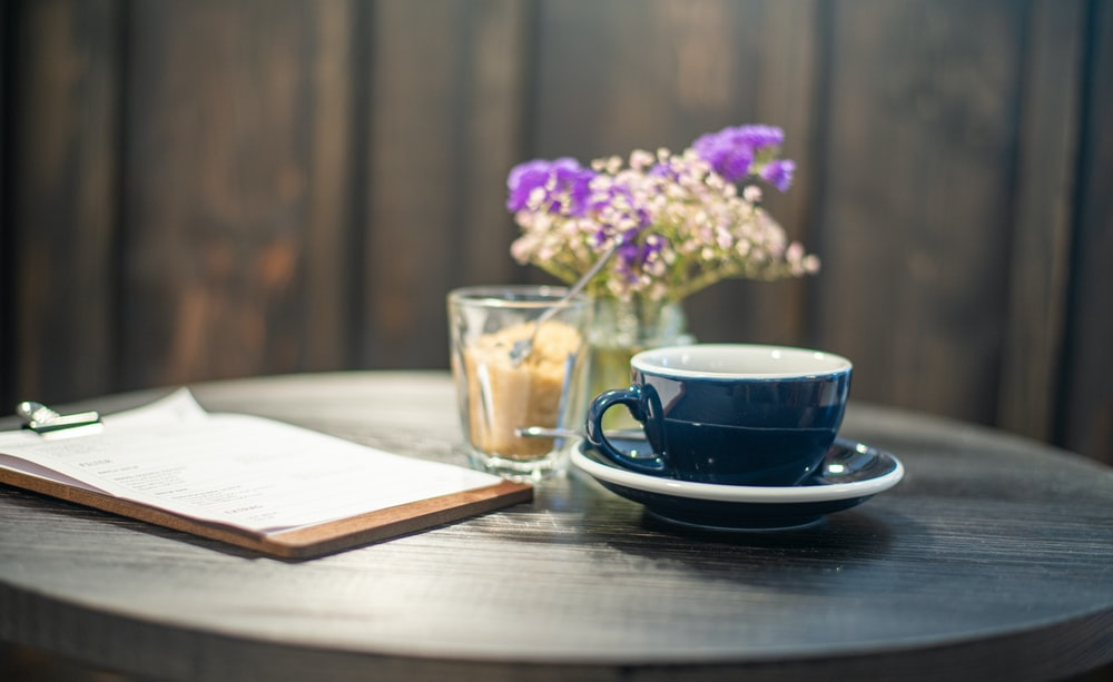 blue ceramic cup on saucer beside purple flowers
