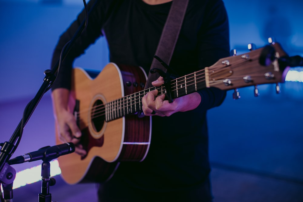 man in black long sleeve shirt playing brown acoustic guitar
