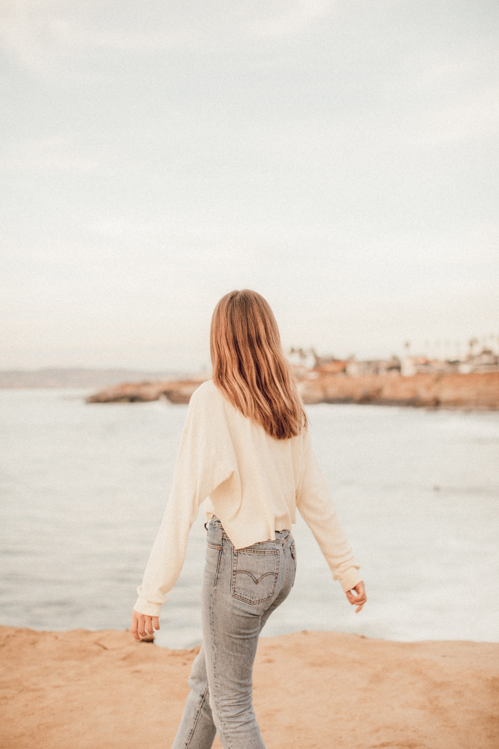 woman in white long sleeve shirt and blue denim jeans standing on seashore during daytime
