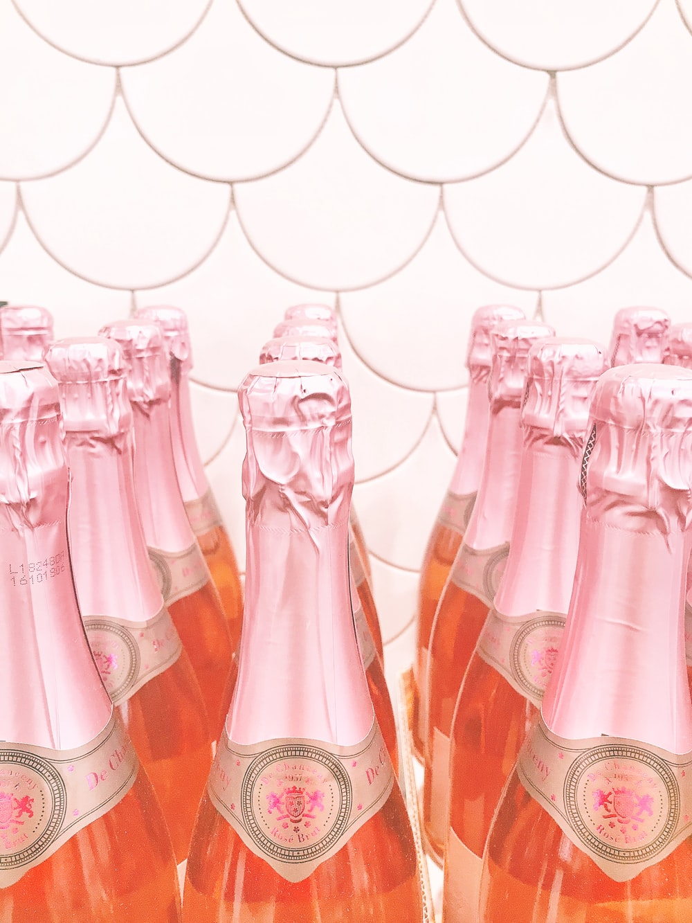 pink glass bottles on brown wooden table