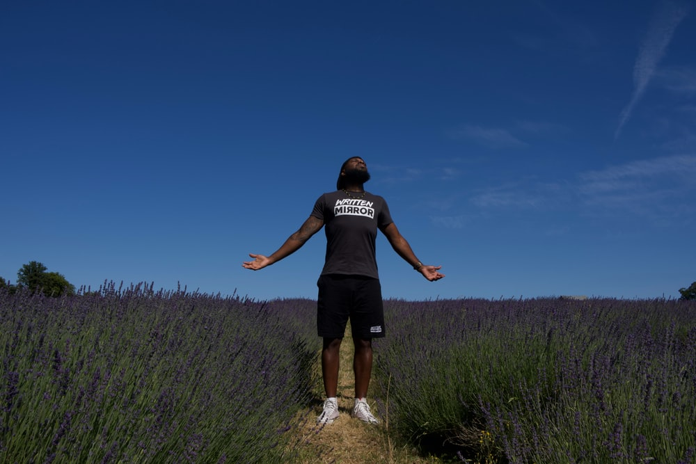 man in black crew neck t-shirt and black shorts standing on green grass field under