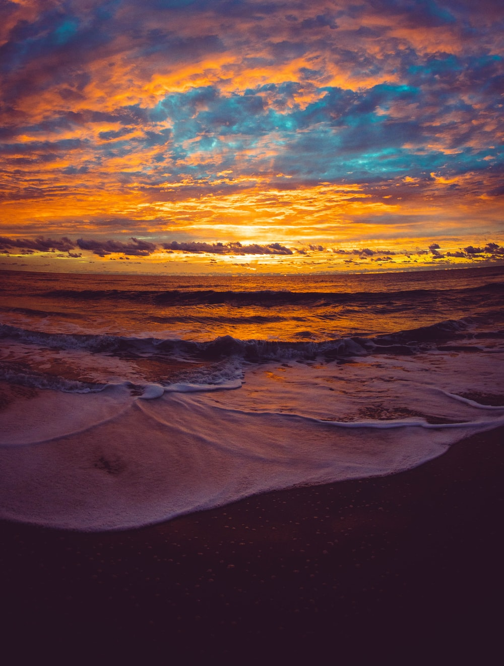 brown and white ocean waves during sunset