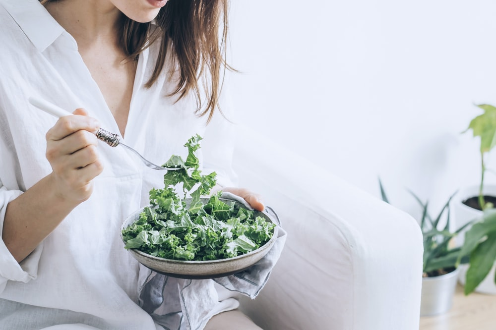 woman in white dress holding silver fork and knife slicing green vegetable on white ceramic bowl