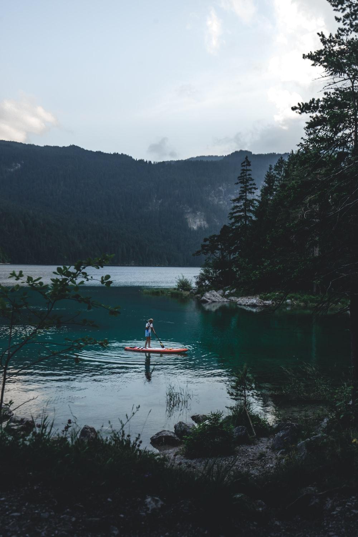 person riding on red kayak on lake during daytime
