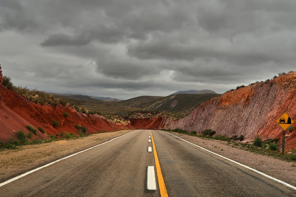 gray concrete road between brown mountains under gray clouds during daytime