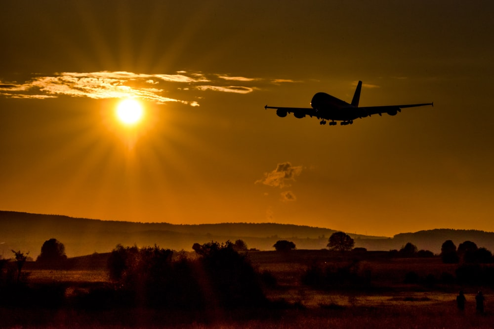silhouette of airplane flying over the field during sunset