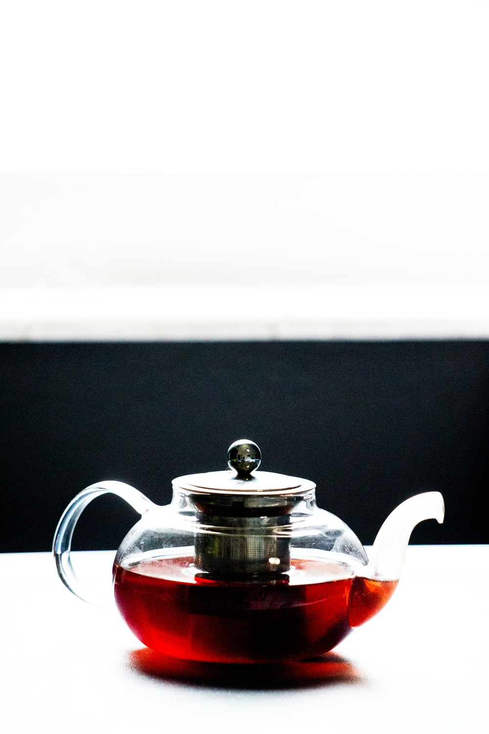 red and silver teapot on black table