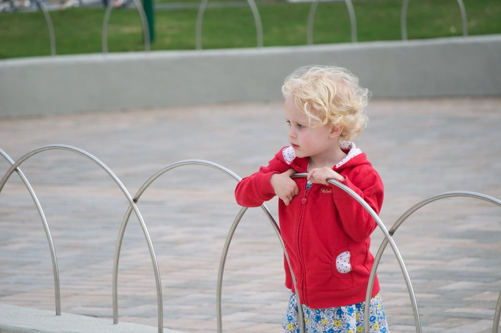 girl in red long sleeve shirt holding red hose