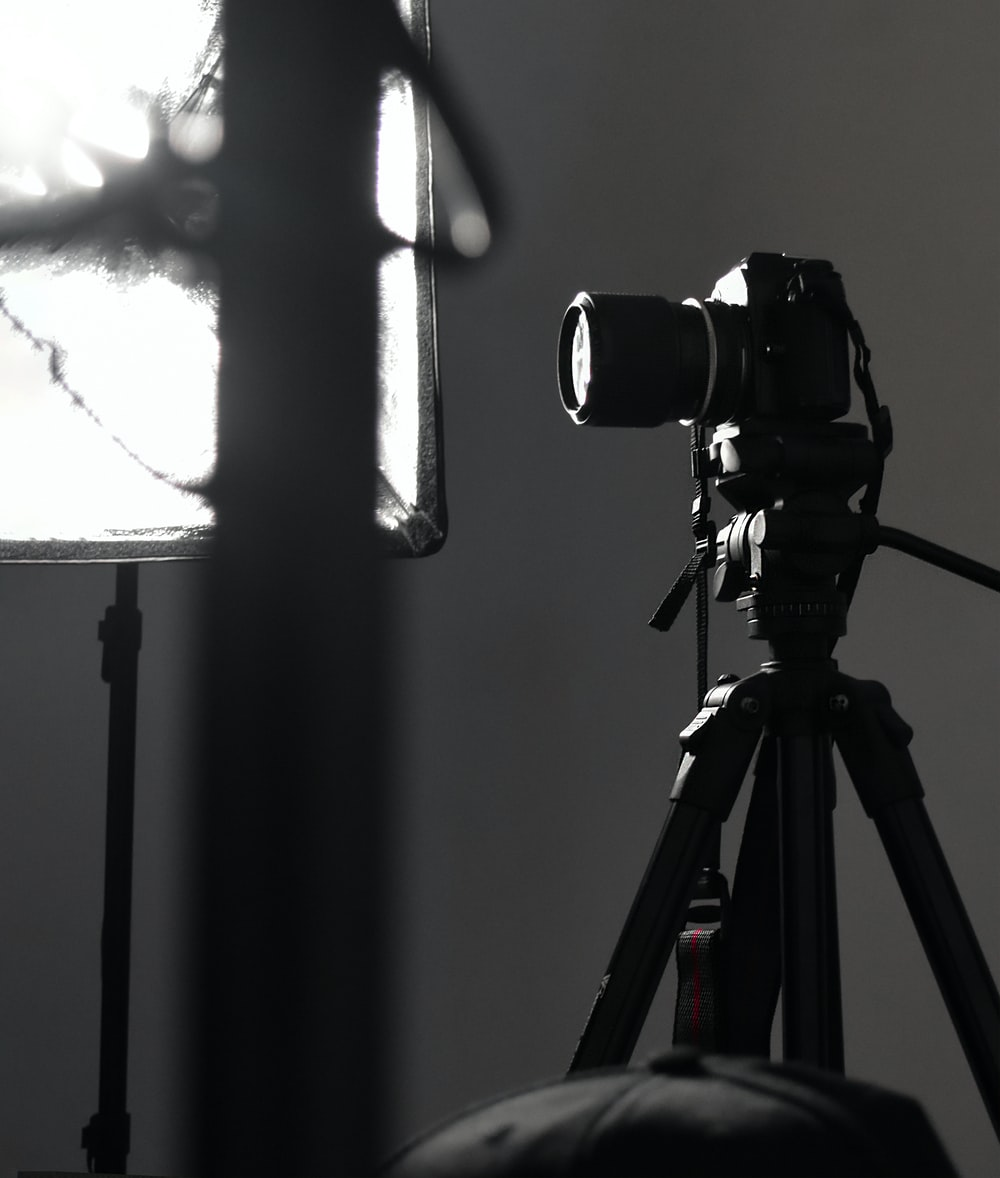 black camera on tripod in grayscale photography