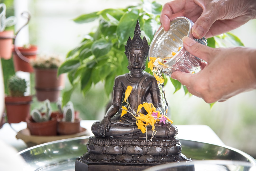 A woman was pouring flower floated water onto the Black Buddha statue.
