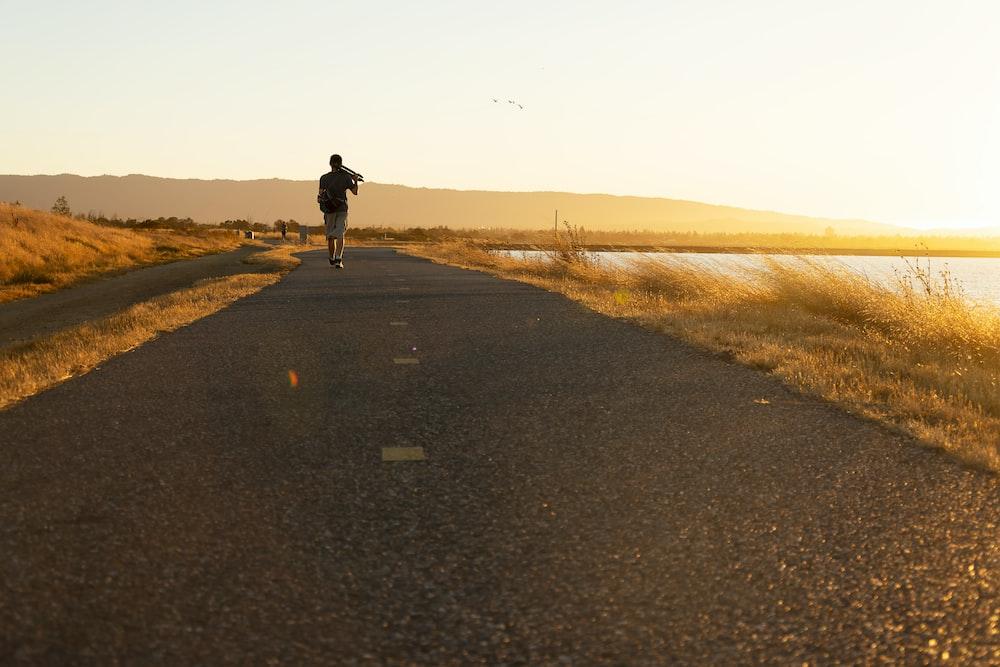 man in black jacket walking on gray asphalt road during daytime