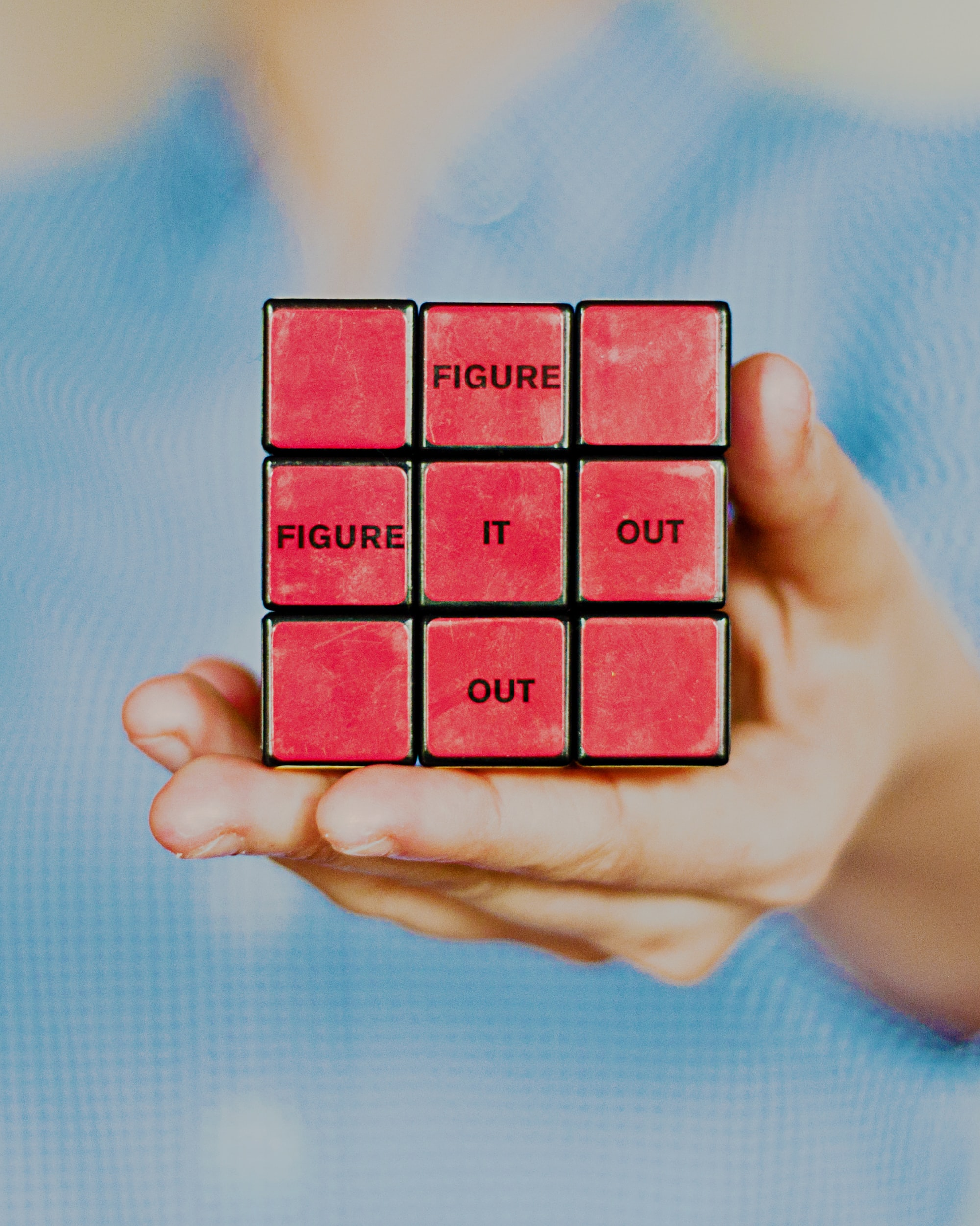 """Person holding a solved rubik's cube with the words """"figure it out""""."""
