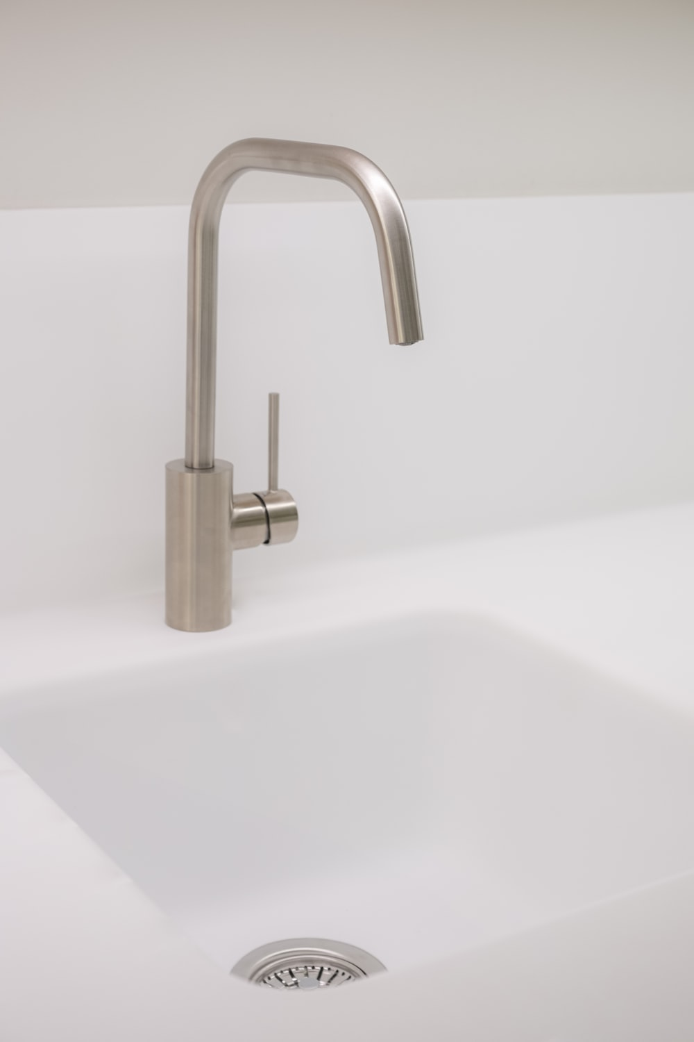 stainless steel faucet on white ceramic sink