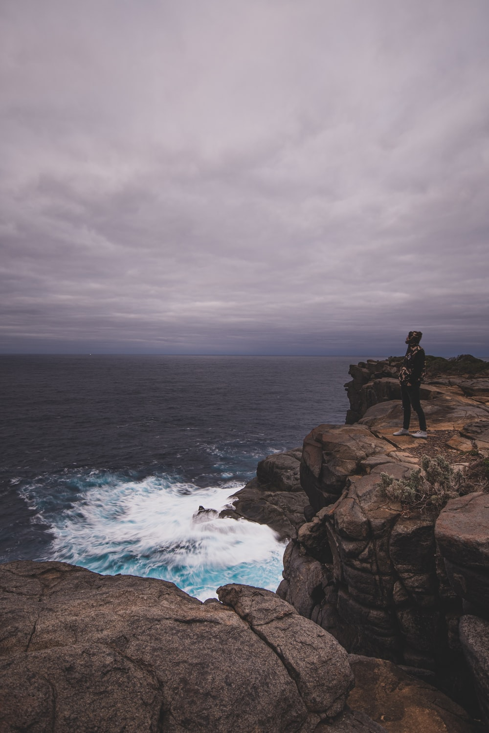 man standing on rock formation near sea during daytime