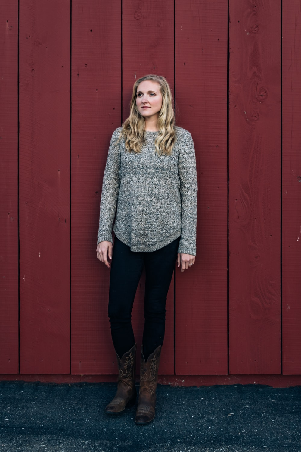 woman in gray sweater standing beside red wooden wall