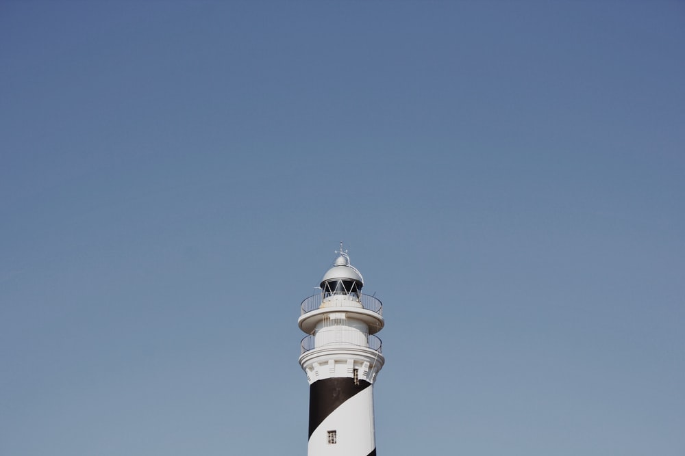 white and black lighthouse under blue sky during daytime