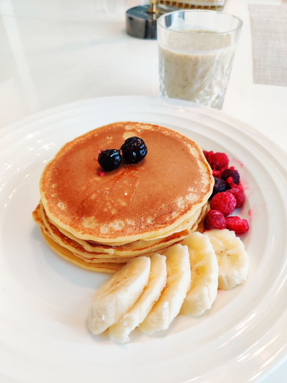 pancakes with berries on white ceramic plate