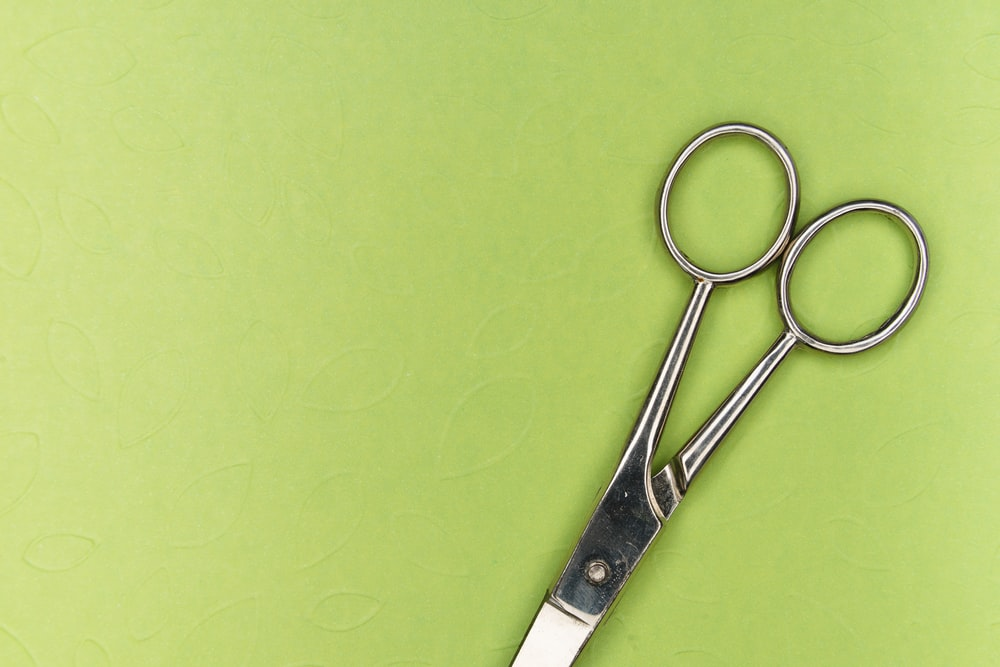 silver scissors on green surface