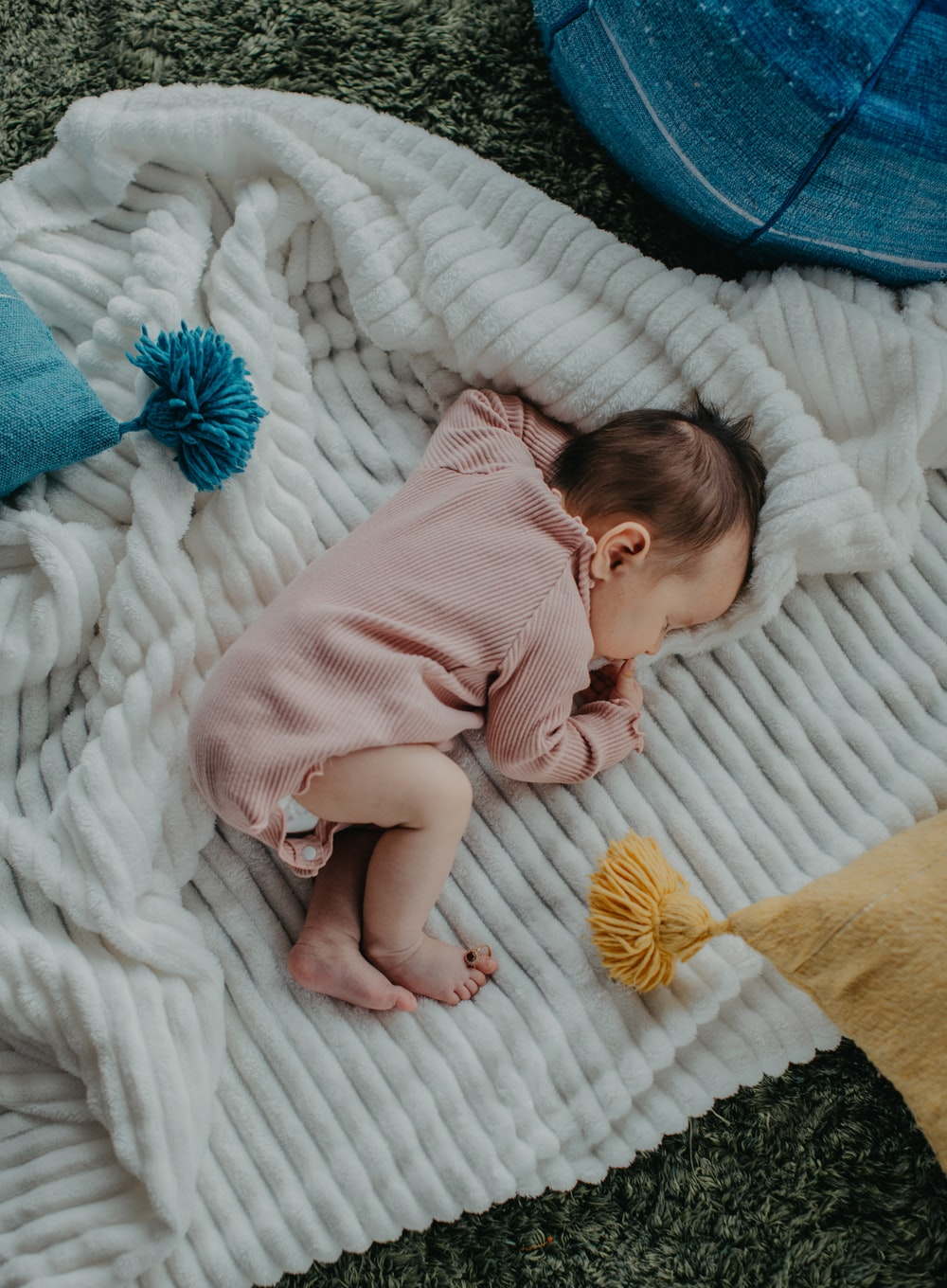 baby in pink onesie lying on white bed
