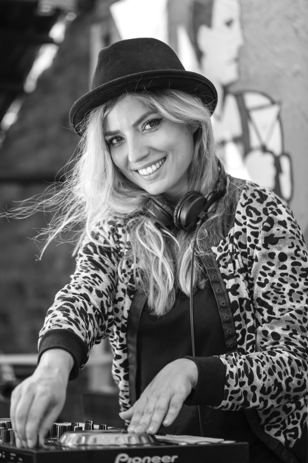 grayscale photo of woman wearing leopard print coat and hat