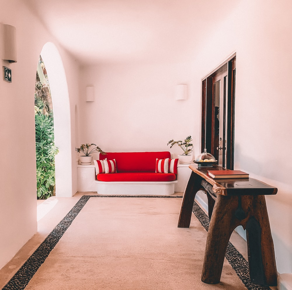 brown wooden table near red sofa