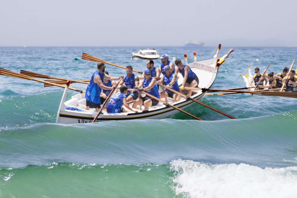 people riding on blue and white boat on sea during daytime