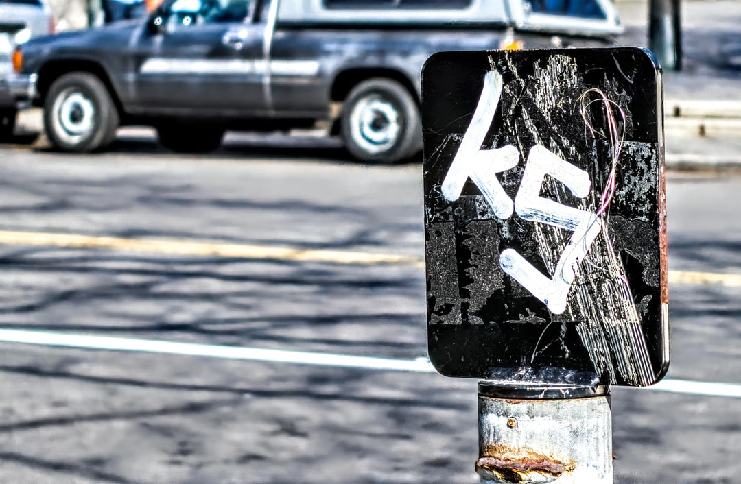 A street sign in Washington DC is covered with graffiti lettering during midday.
