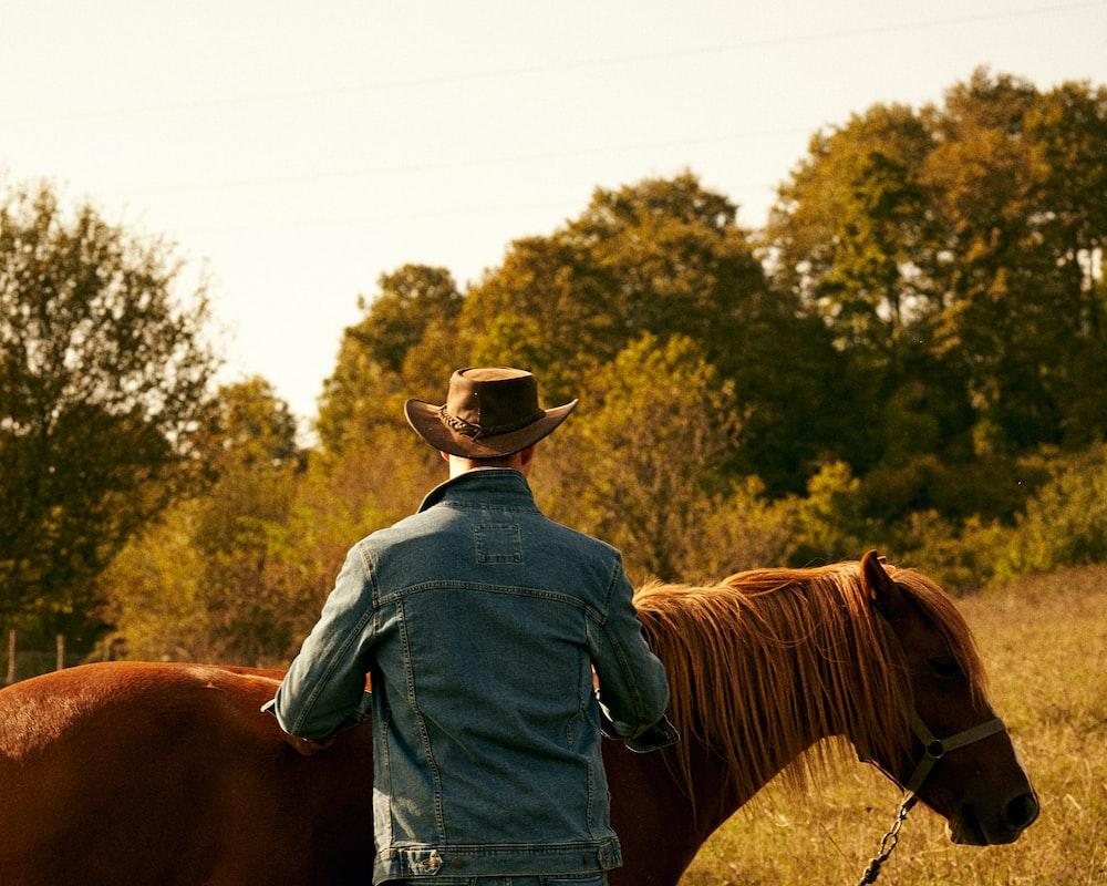 man in blue denim jacket wearing brown cowboy hat riding brown horse during daytime