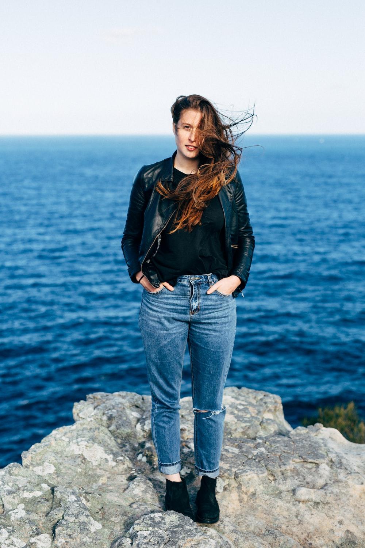 woman in black leather jacket and blue denim jeans standing on gray rock near body of near near near near
