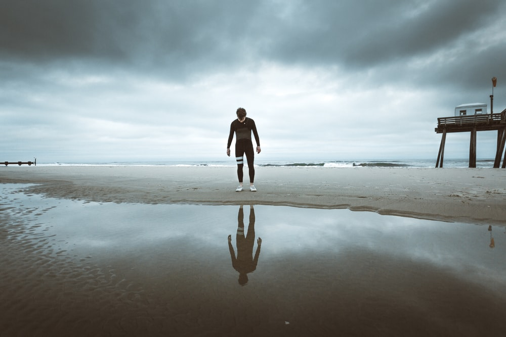 woman in black long sleeve shirt and black pants walking on seashore during daytime