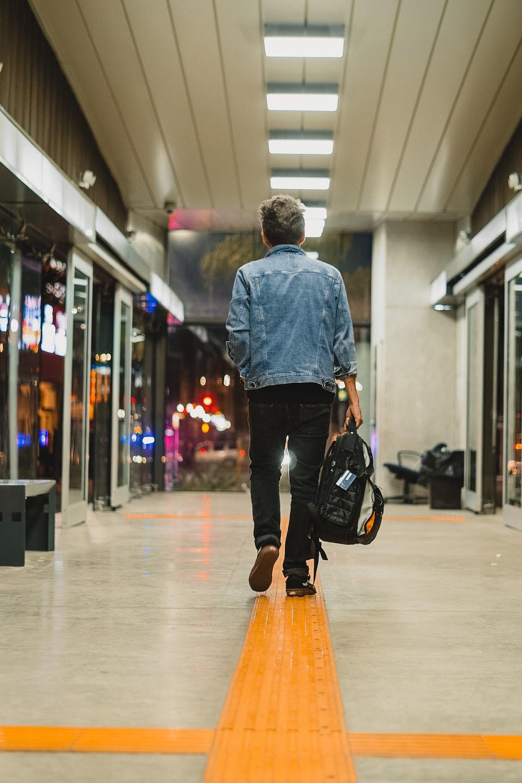 man in blue dress shirt and black pants walking on hallway
