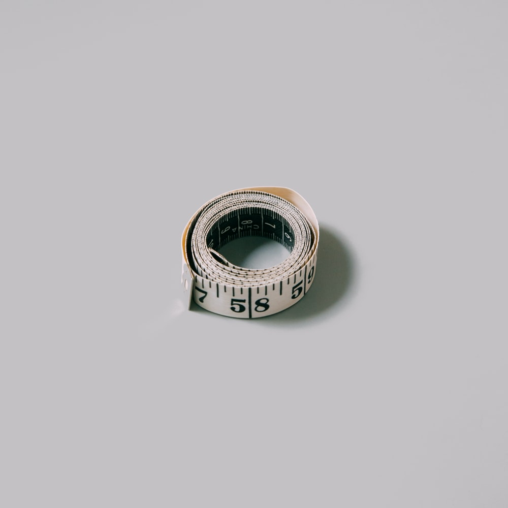 silver and gold ring on white surface