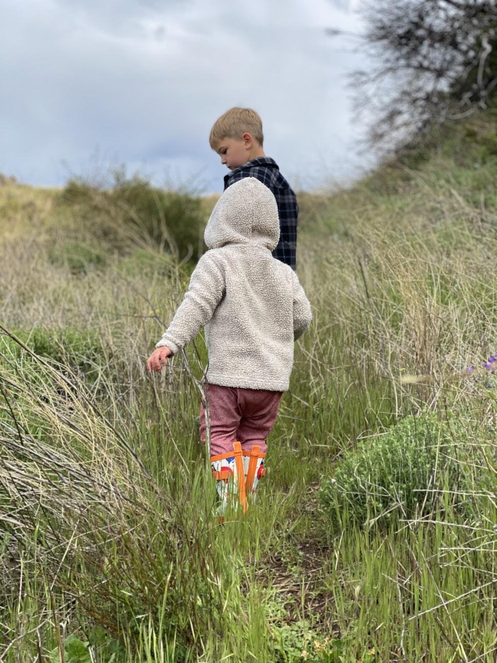 boy in gray hoodie walking on green grass field during daytime