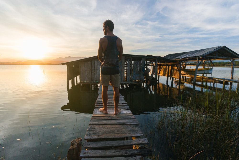 woman in white tank top and blue denim shorts standing on wooden dock during daytime