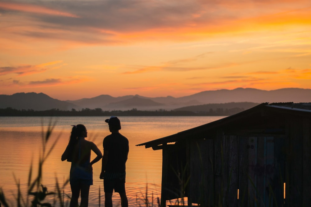 silhouette of 2 women standing on wooden dock during sunset
