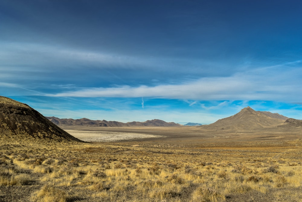brown grass field near brown mountain under blue sky during daytime