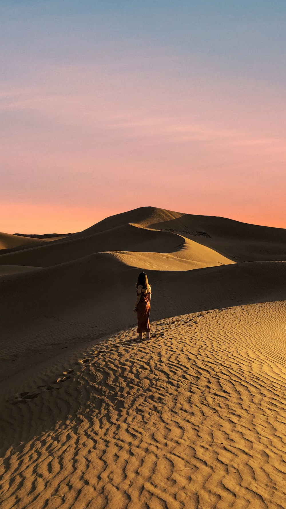 woman in black dress walking on desert during daytime