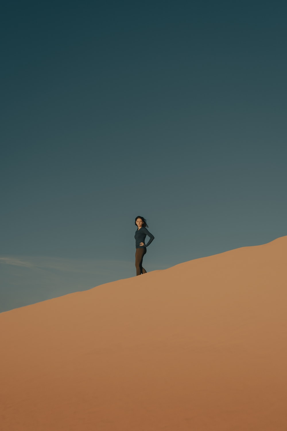 woman in black shirt and black shorts standing on brown sand during daytime