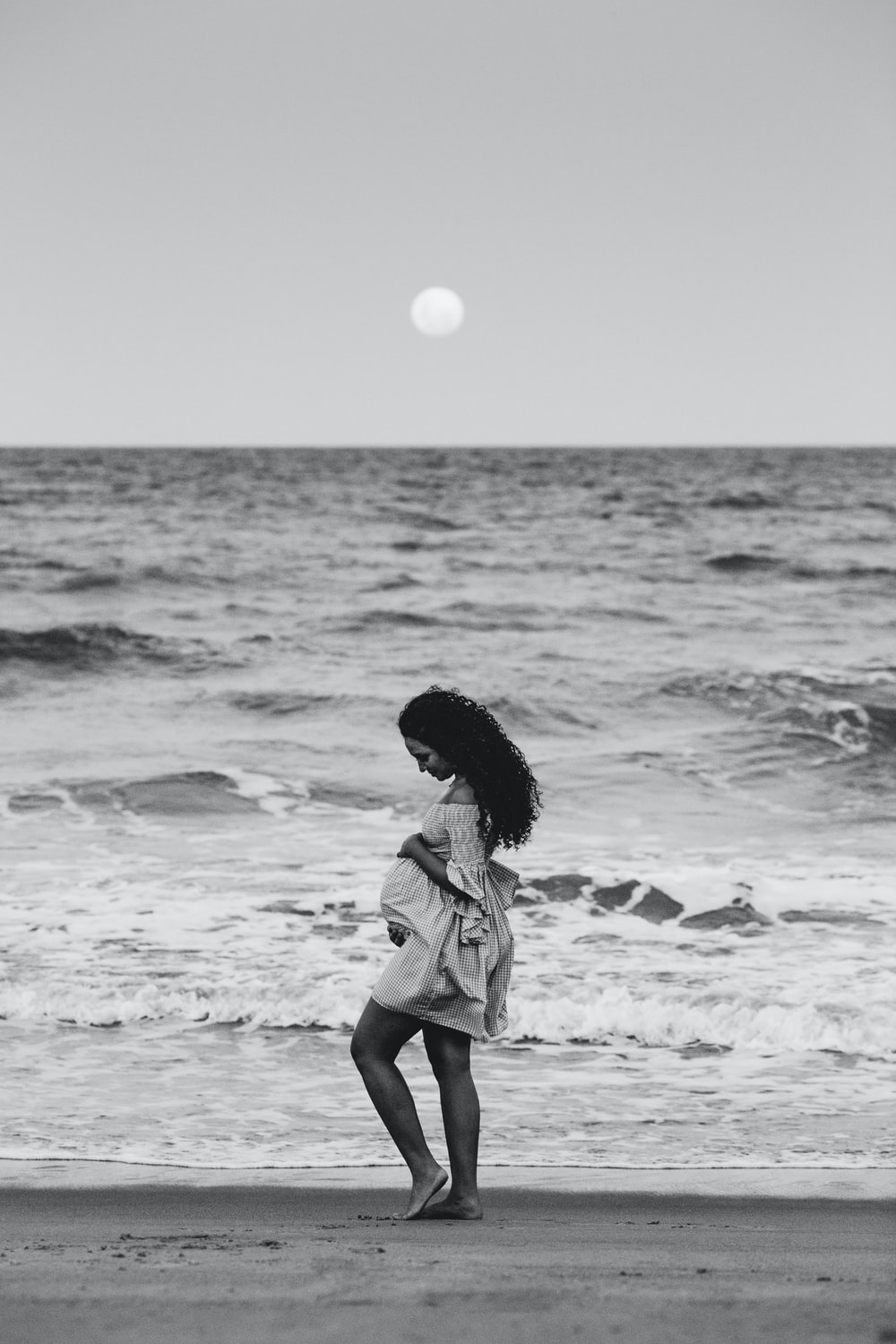 girl in white and black dress standing on seashore during daytime