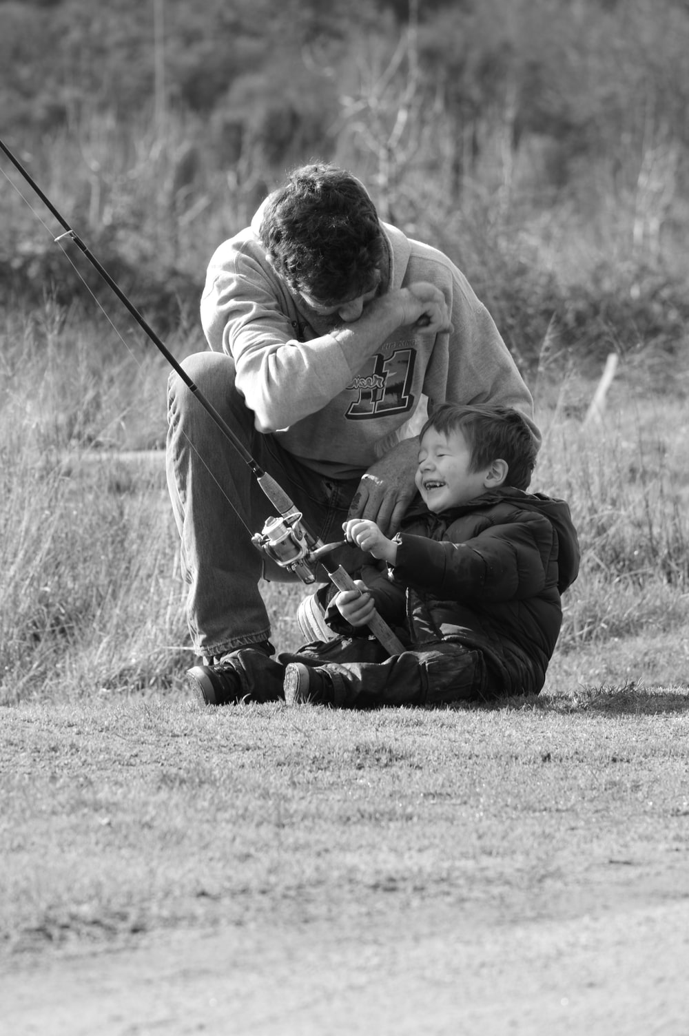 grayscale photo of man in hoodie playing with a baby