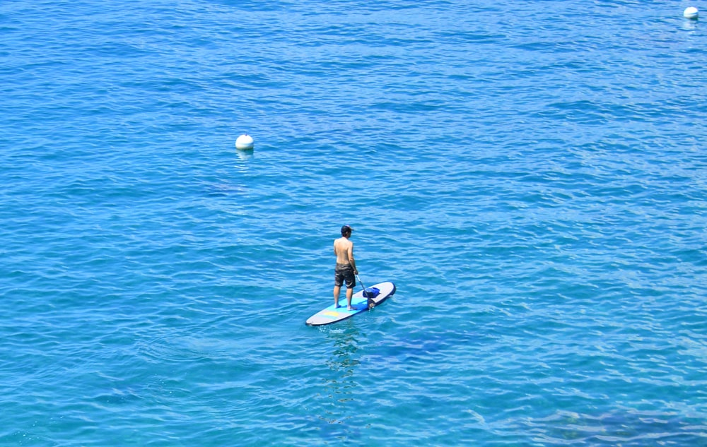 woman in black bikini riding on blue surfboard during daytime