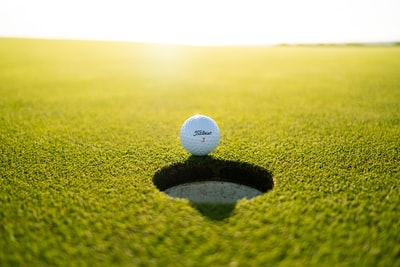 golf ball on green grass field during daytime golf teams background