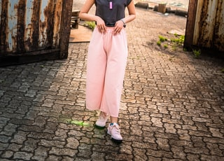 woman in black tank top and pink pants standing on brown brick floor during daytime