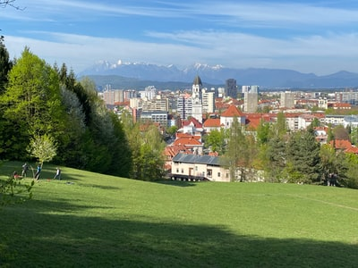Ljubljana brown and white concrete houses near green trees under blue sky during daytime